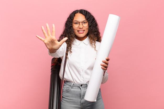 若いヒスパニック系の女性は笑顔でフレンドリーに見え、前に手を出して5番または5番を示し、カウントダウンします。建築家の概念