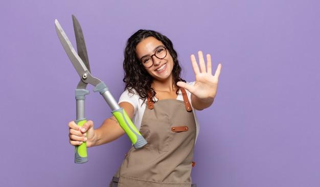 若いヒスパニック系の女性が笑顔でフレンドリーに見え、手を前に向けて5番または5番を示し、カウントダウン
