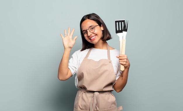 Молодая латиноамериканская женщина улыбается и выглядит дружелюбно, показывая номер пять или пятое с рукой вперед, отсчитывая