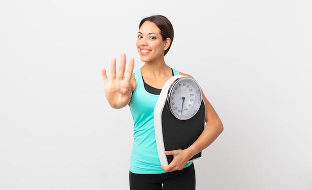 젊은 히스패닉계 여성이 웃고 친절해 보이며 4번을 보여주고 체중계를 들고 있습니다.
