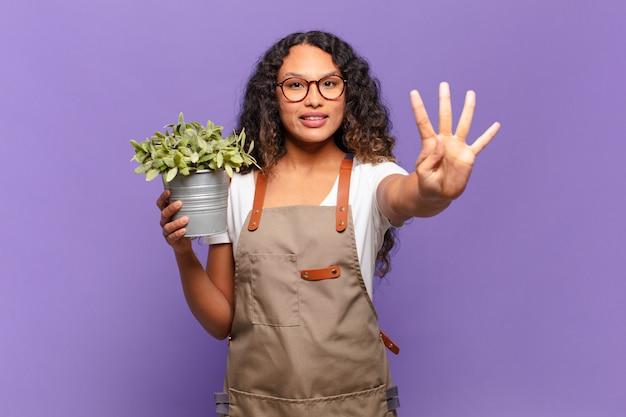 Молодая латиноамериканская женщина улыбается и выглядит дружелюбно, показывает номер четыре или четвертый с рукой вперед, отсчитывая. концепция садовника