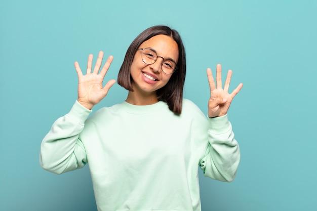 Молодая латиноамериканская женщина улыбается и выглядит дружелюбно, показывает номер девять или девятое с рукой вперед, отсчитывая