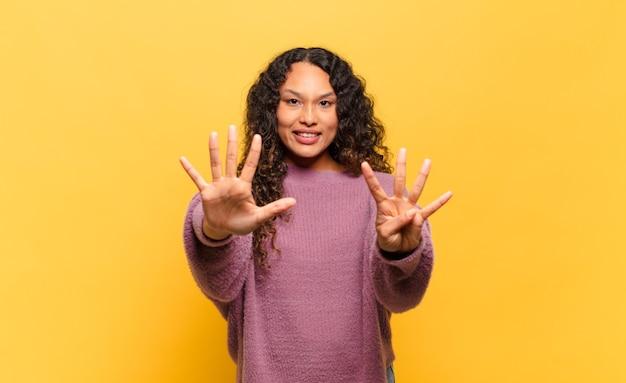 若いヒスパニック系の女性が笑顔でフレンドリーに見え、前に手を出して9番または9番を示し、カウントダウン