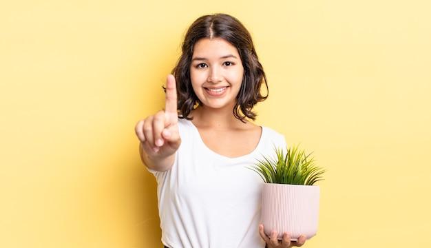 Молодая латиноамериканская женщина улыбается и выглядит дружелюбно, показывая номер один. концепция роста