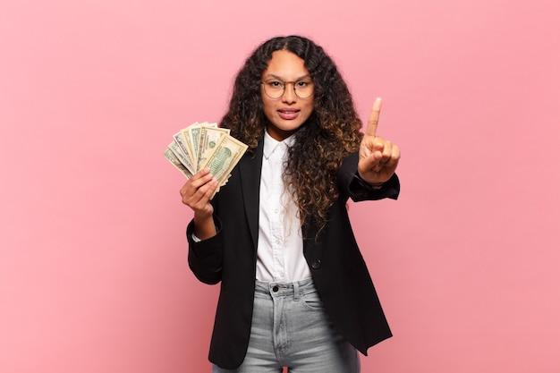 Молодая латиноамериканская женщина улыбается и выглядит дружелюбно, показывает номер один или первый с рукой вперед, отсчитывая. доллар банкноты концепция