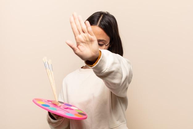 Молодая латиноамериканская женщина улыбается и выглядит дружелюбно, показывает номер шесть или шестой рукой вперед, отсчитывая