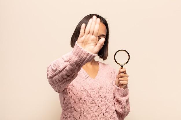 젊은 히스패닉 여자 웃 고 친절 하 게 찾고, 앞으로 손으로 숫자 10 또는 10을 보여주는 카운트 다운
