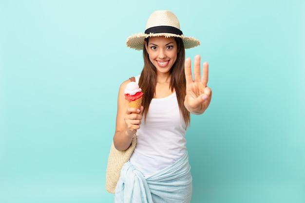 Молодая латиноамериканская женщина улыбается и выглядит дружелюбно, показывает номер три и держит мороженое. концепция шумер