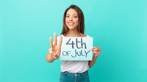 Молодая испаноязычная женщина улыбается и выглядит дружелюбно, показывая номер три. концепция дня независимости