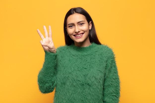Молодая латиноамериканская женщина улыбается и выглядит дружелюбно, показывает номер три или треть рукой вперед и ведет обратный отсчет