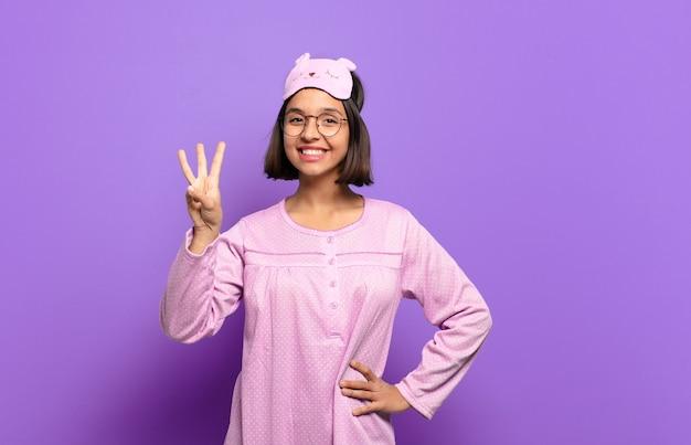 Молодая латиноамериканская женщина улыбается и выглядит дружелюбно, показывая номер три или треть рукой вперед