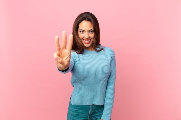 Молодая латиноамериканская женщина улыбается и выглядит дружелюбно, показывая номер три