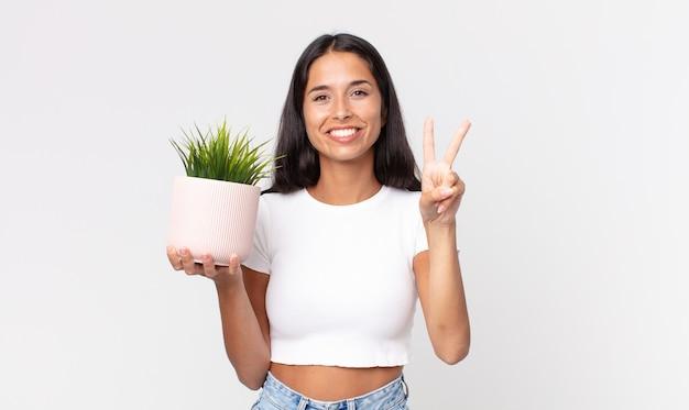 Молодая латиноамериканка улыбается и выглядит дружелюбно, показывая номер два и держит декоративное домашнее растение