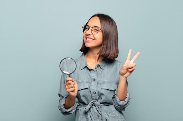 젊은 히스패닉 여자 웃 고 친절 하 게 찾고, 앞으로 손으로 번호 2 또는 초를 보여주는 카운트 다운
