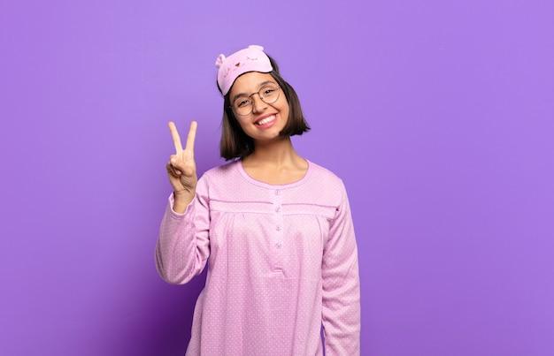 笑顔でフレンドリーに見える若いヒスパニック系女性、前に手を前に2番目または2番目を示し、カウントダウン
