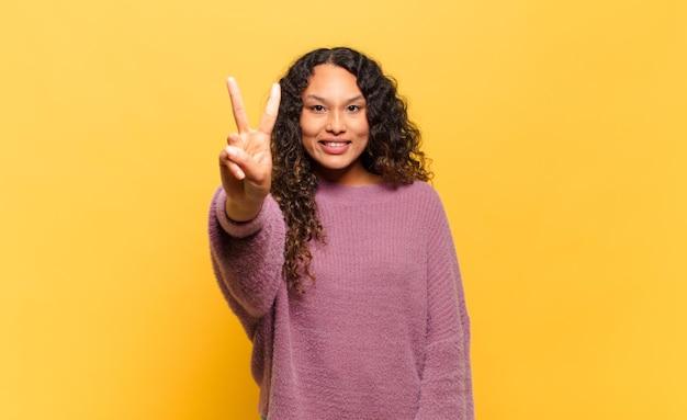 Молодая латиноамериканка улыбается и выглядит дружелюбно, показывает номер два или секунду рукой вперед, отсчитывая