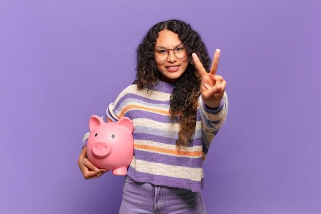 若いヒスパニック系の女性は笑顔で幸せそうに見え、のんきで前向きで、片手で勝利または平和を身振りで示します。貯金箱のコンセプト