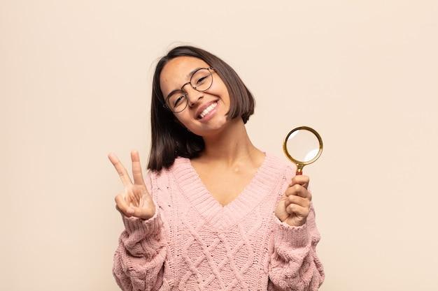 젊은 히스패닉 여자 웃고 행복하고 평온하고 긍정적 인 찾고 한 손으로 승리 또는 평화 몸짓