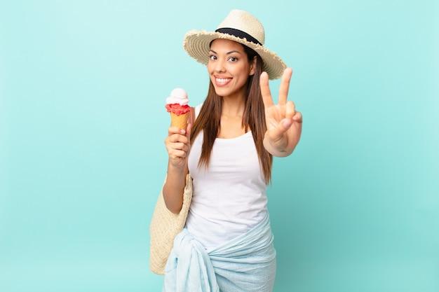 Молодая латиноамериканская женщина улыбается и выглядит счастливой, жестикулирует победу или мир и держит мороженое. концепция шумер