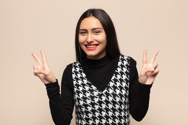 Молодая латиноамериканская женщина улыбается и выглядит счастливой