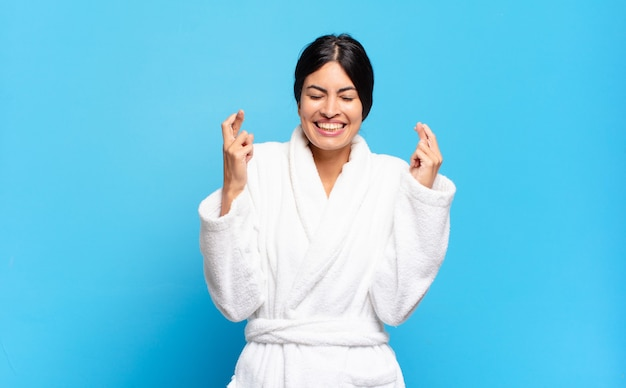 Young hispanic woman smiling and anxiously crossing both fingers, feeling worried and wishing or hoping for good luck. bathrobe concept