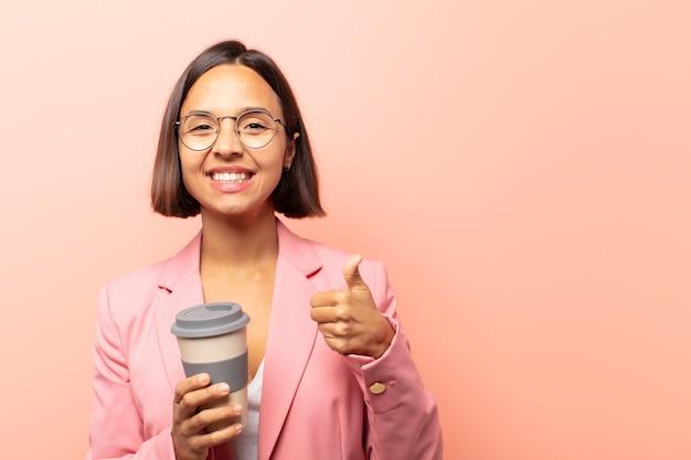 두 엄지 손가락으로 광범위하게 행복하고 긍정적이며 자신감 있고 성공적인 찾고 웃는 젊은 히스패닉 여성