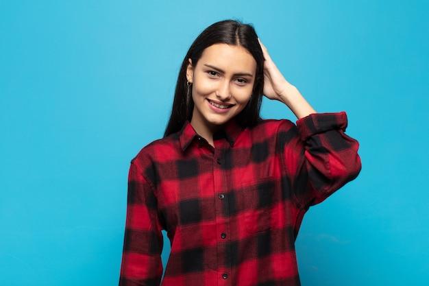 Молодая латиноамериканка весело и небрежно улыбается, взявшись за голову с позитивным, счастливым и уверенным взглядом