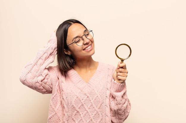 쾌활하고 부담없이 웃고 긍정적이고 행복하고 자신감있는 표정으로 머리에 손을 잡고 젊은 히스패닉 여성