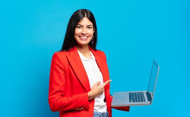 Молодая латиноамериканская женщина весело улыбается, чувствует себя счастливой и указывает в сторону и вверх, показывая объект в копировальном пространстве. концепция ноутбука