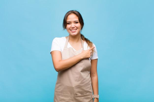 若いヒスパニック系の女性は元気に笑って、幸せを感じて、横と上を指して、コピースペースにオブジェクトを表示します。