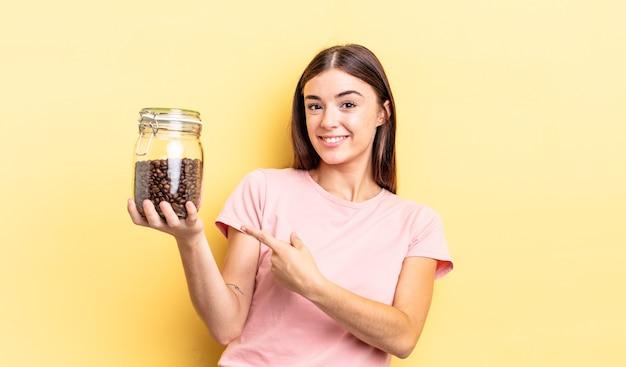 젊은 히스패닉계 여성이 유쾌하게 웃고 행복하며 옆을 가리키고 있습니다. 커피 콩 개념