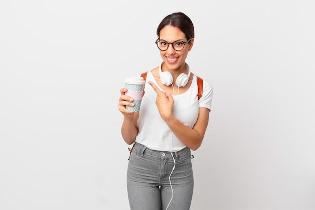 Молодая латиноамериканская женщина весело улыбается, чувствуя себя счастливой и указывая в сторону. студенческая концепция