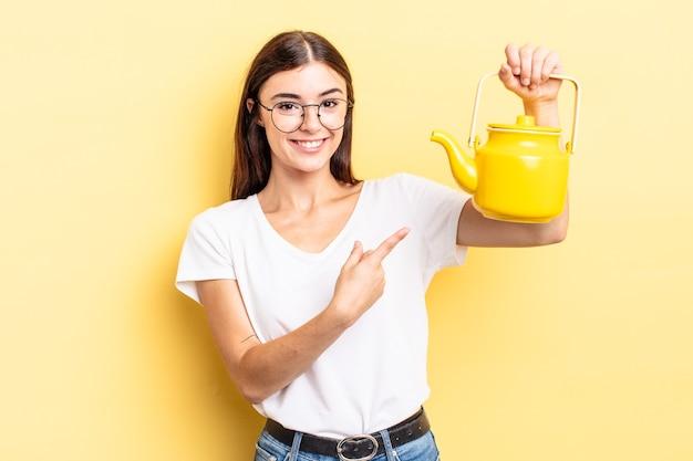 Молодая латиноамериканская женщина весело улыбается, чувствуя себя счастливой и указывая в сторону. концепция чайника