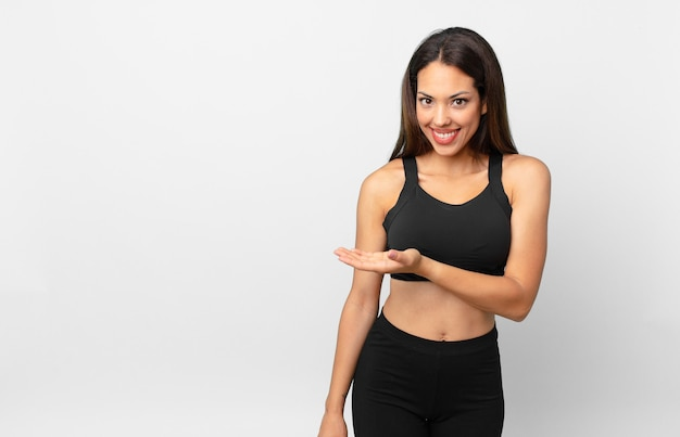 Молодая латиноамериканская женщина весело улыбается, чувствует себя счастливой и показывает концепцию. фитнес-концепция