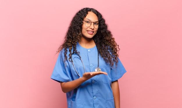 Молодая латиноамериканская женщина весело улыбается, чувствует себя счастливой и показывает концепцию в копировальном пространстве с ладонью. концепция медсестры