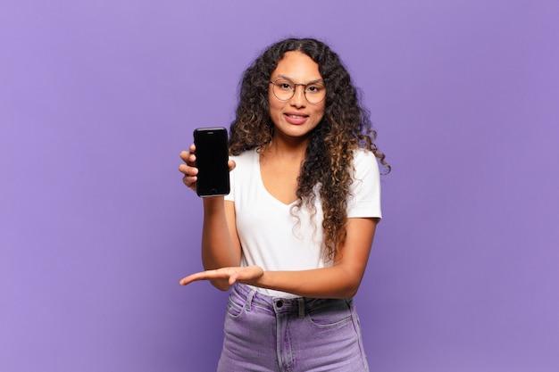 陽気な笑顔、幸せを感じ、手のひらでコピースペースでコンセプトを示す若いヒスパニック系女性。スマートフォンのコンセプト