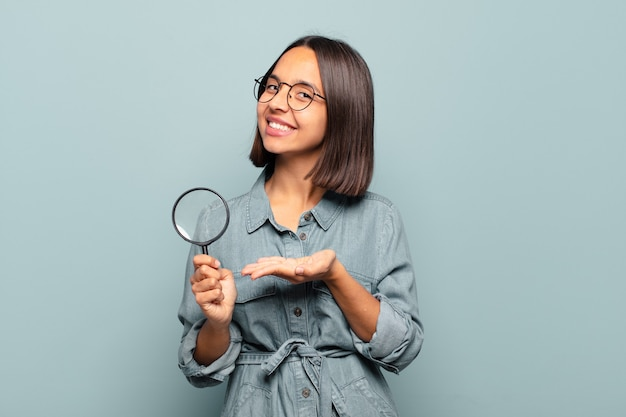 유쾌하게 웃고, 행복감을 느끼고 손바닥으로 복사 공간에 개념을 보여주는 젊은 히스패닉 여자