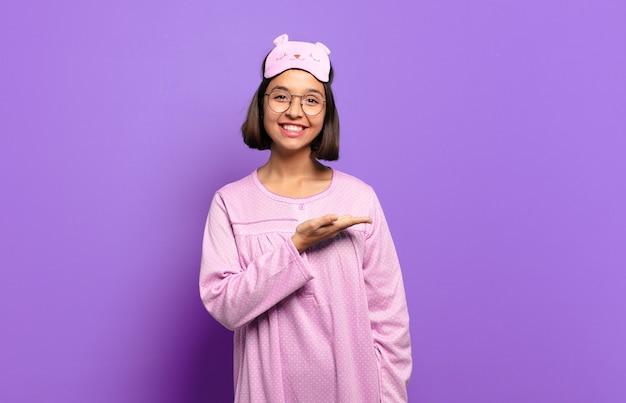 陽気な笑顔、幸せを感じ、手のひらでコピースペースでコンセプトを示す若いヒスパニック系女性
