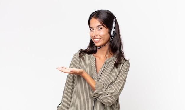 젊은 히스패닉계 여성이 유쾌하게 웃고 행복하며 헤드셋으로 개념을 보여줍니다. 텔레마케팅 개념