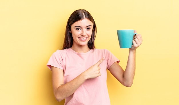 Young hispanic woman smiling cheerfully, feeling happy and pointing to the side. coffee cup concept