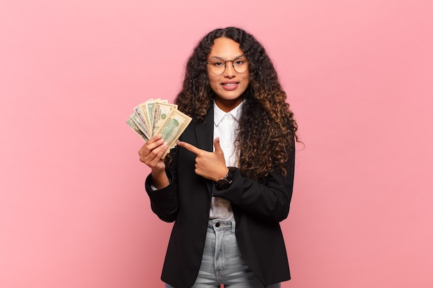 Young hispanic woman smiling cheerfully, feeling happy and pointing to the side and upwards, showing object in copy space. dollar banknotes concept