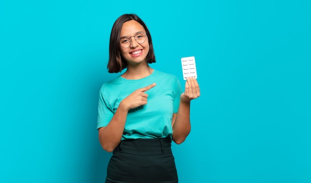 Young hispanic woman smiling cheerfully, feeling happy and pointing to the side and upwards, showing object in copy space
