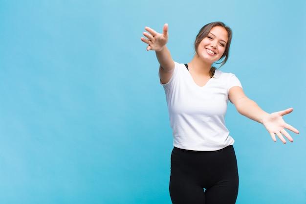 Молодая латиноамериканская женщина весело улыбается, давая теплые, дружеские, любящие приветственные объятия, чувствуя себя счастливой и очаровательной