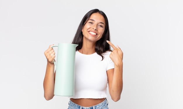Young hispanic woman smiling confidently pointing to own broad smile and holding a coffee thermos