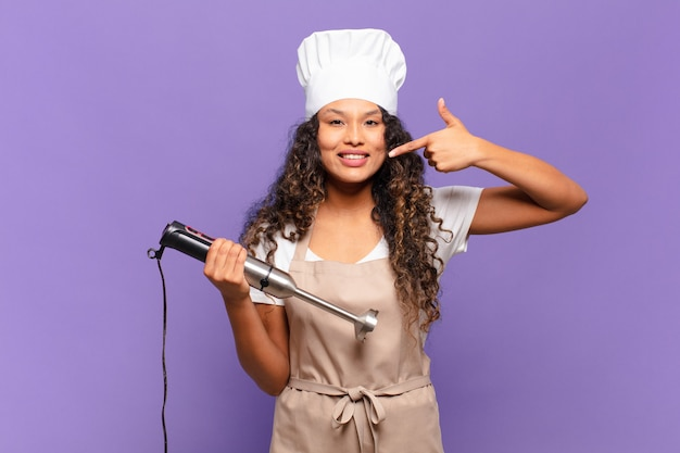 자신의 넓은 미소, 긍정적이고 편안하며 만족스러운 태도를 자신있게 가리키며 웃고 있는 젊은 히스패닉 여성. 요리사 개념