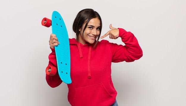 Молодая латиноамериканская женщина уверенно улыбается, указывая на собственную широкую улыбку, позитивное, расслабленное, удовлетворенное отношение