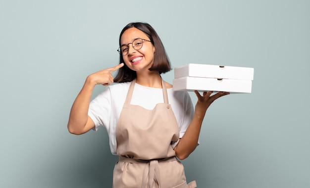 自信を持って笑顔の若いヒスパニック系女性は、自分の広い笑顔、前向きで、リラックスした、満足のいく態度を指しています