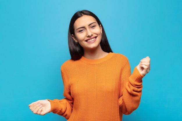 若いヒスパニック系女性は笑顔、のんきな気分、リラックスして幸せ、ダンスと音楽を聴いて、パーティーで楽しんでいます