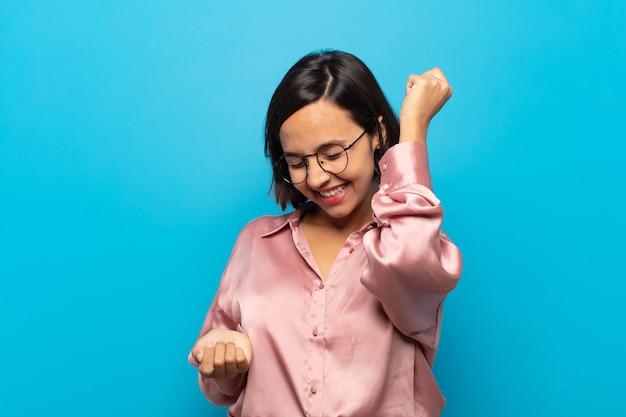 笑顔、のんきな気分、リラックスして幸せ、ダンスと音楽を聴いて、パーティーで楽しんでいる若いヒスパニック系女性