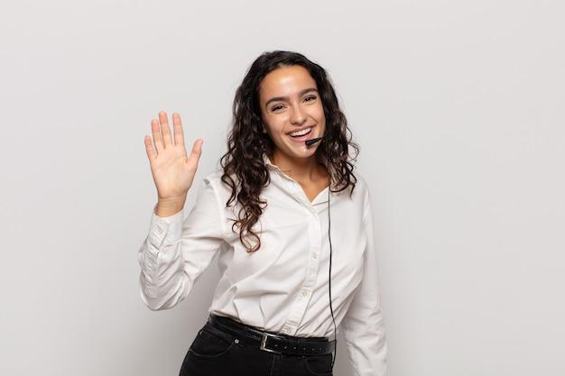 행복하고 유쾌하게 웃고, 손을 흔들며, 환영하고 인사하거나, 작별 인사를하는 젊은 히스패닉 여성